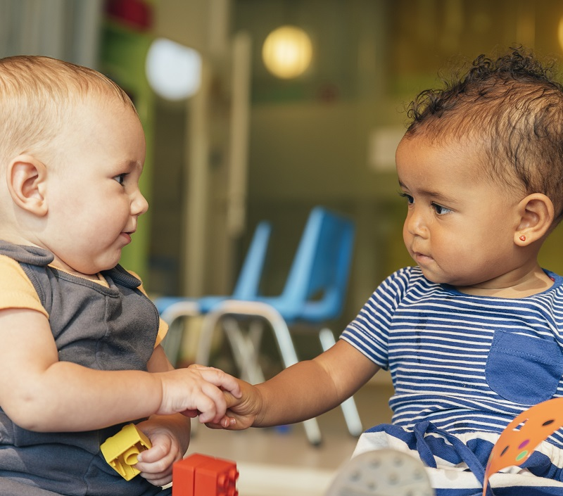 two toddler babies at day care holding hands