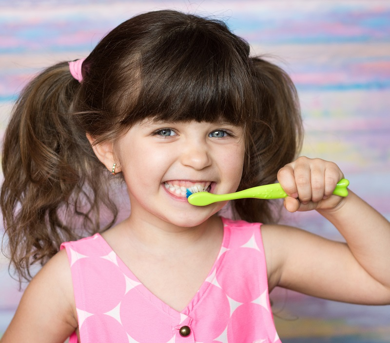 pretty little girl smiling with lime green tooth brush